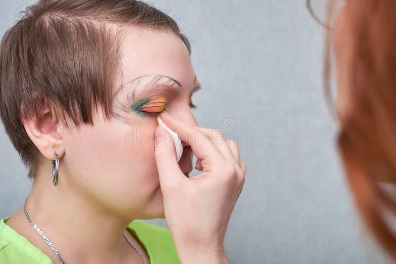 Artista professionista di volto che applica trucco artistico sul fronte del ` s della donna in salone immagini stock libere da diritti