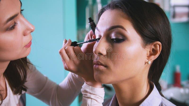 Artista profissional da cara que faz a composição com lápis de olho preto para a mulher bonita imagens de stock royalty free