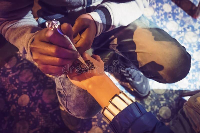 Artista que aplica diseño árabe del tatuaje hermoso de la alheña a una mujer o a las manos de la novia india en fotografía de archivo libre de regalías