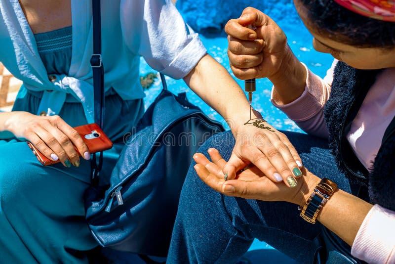 Artista que aplica el tatuaje de la alheña en las manos de las mujeres en las calles de Marrakesh, Marruecos fotos de archivo