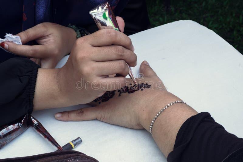 Artista que aplica el tatuaje de la alheña en la mano de las mujeres fotografía de archivo