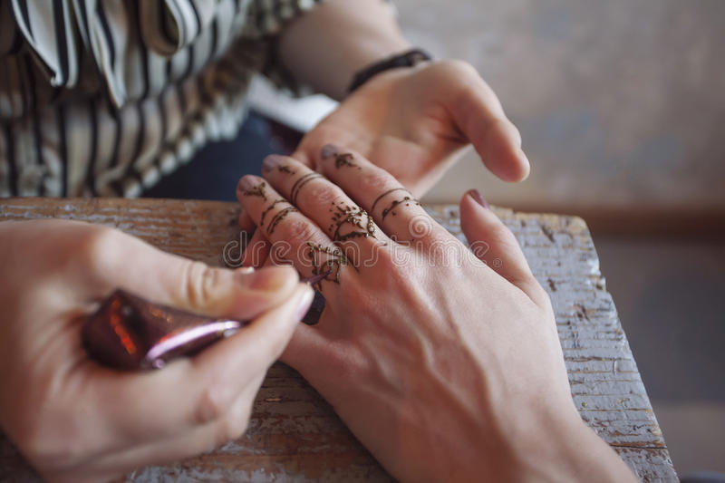 Artista que aplica a tatuagem da hena nas mãos das mulheres imagem de stock