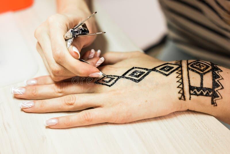 Artista que aplica a tatuagem da hena nas mãos das mulheres Mehndi é arte decorativa indiana tradicional Close-up fotografia de stock royalty free