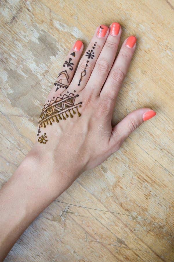 Artista que aplica a tatuagem da hena nas mãos das mulheres Mehndi é arte decorativa indiana tradicional Close-up, vista aérea -  imagem de stock royalty free