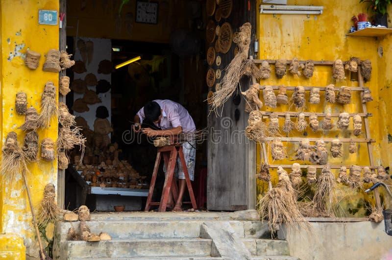 Artista que cinzela as cabeças humanas feitas de raizes de madeira imagem de stock royalty free