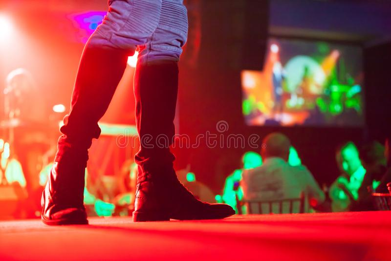 Artista que executa na fase que veste suas botas bonitas quando o convidado tiver o jantar foto de stock