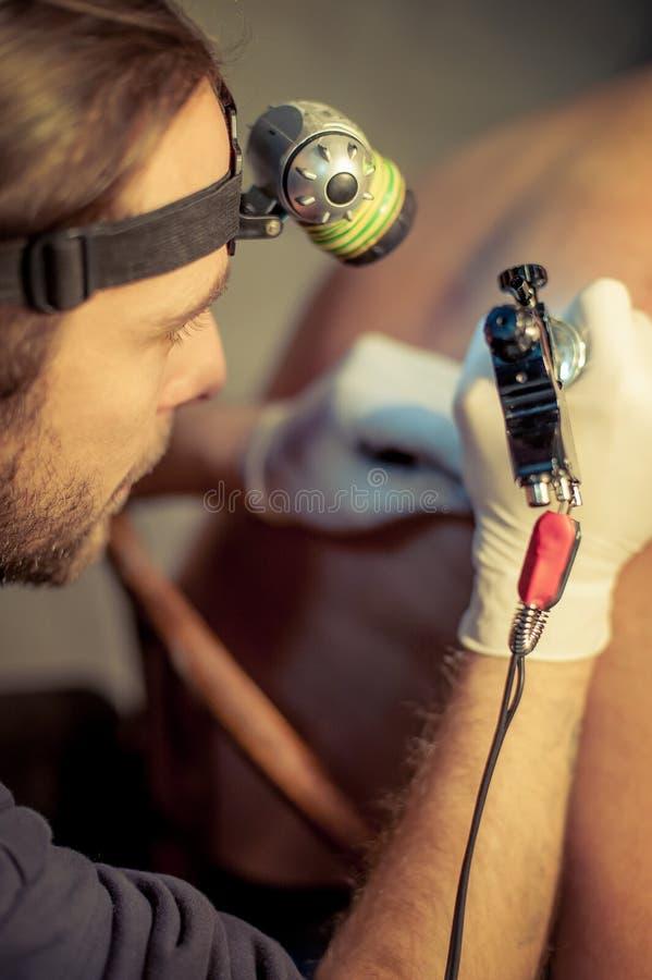 Artista que hace el tatuaje en el cliente masculino foto de archivo libre de regalías