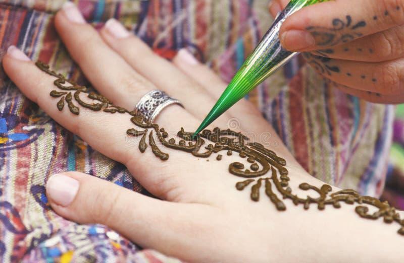 Artista que pinta el tatuaje indio tradicional de la alheña en la mano de la mujer imágenes de archivo libres de regalías