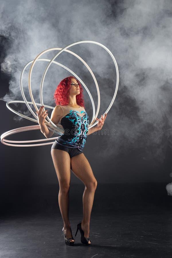 Artista rojo de sexo femenino hermoso del circo del pelo que sostiene aros fotos de archivo