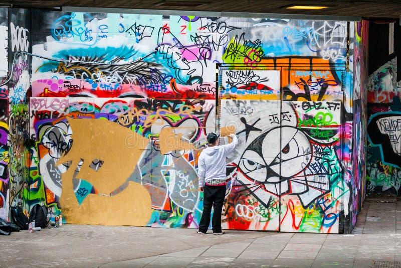 Artista Spraying Paint de la pintada en la pared fotos de archivo libres de regalías