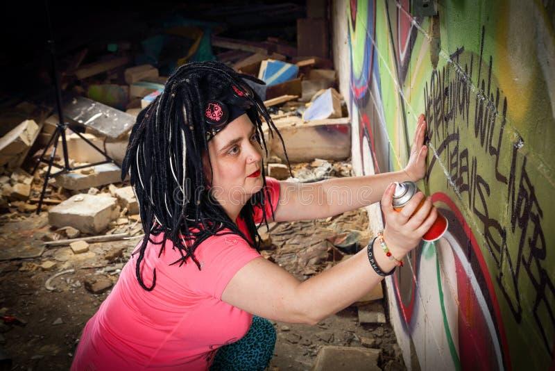 Artista Spraying Wall de la pintada en el edificio abandonado fotos de archivo libres de regalías