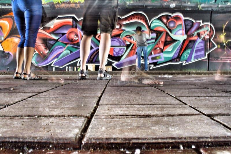 Artista in tensione dei graffiti sul lavoro immagine stock