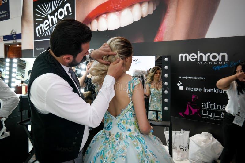 Artista y peluquero de maquillaje que aplican maquillaje profesional en una mujer rubia joven en un vestido colorido fotografía de archivo