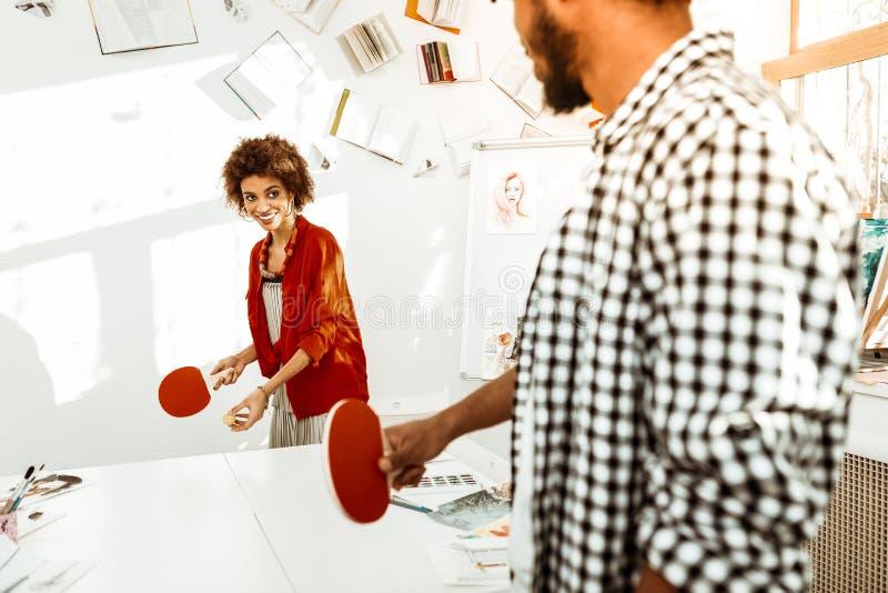 Artistas creativos que tienen cierto resto mientras que juega a tenis de mesa imagenes de archivo