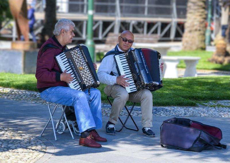 Artistas da rua que jogam os acordeões que esperam para doações nos jardins pelo mar, Santa Margherita Ligure, Itália imagens de stock