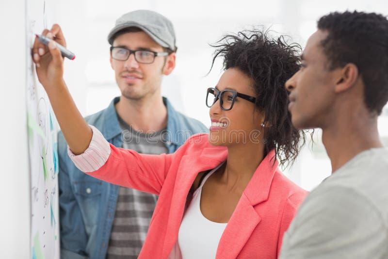 Artistas en la discusión delante del whiteboard fotos de archivo