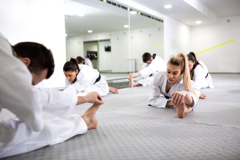 Artistas marciais que fazem separações do pé ao aquecer-se para a prática de taekwondo imagens de stock