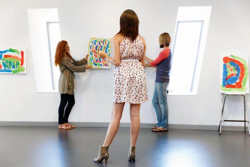 Artistas novos na pintura de suspensão da galeria em paredes foto de stock