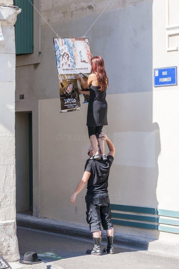 Artistas que penduram cartazes Homem que guarda a mulher em seus ombros fotos de stock royalty free