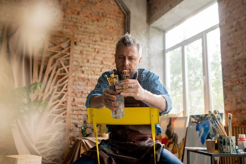 Artiste contemporain d'âge moyen assis sur sa chaise en studio et choisissant le pinceau photo libre de droits