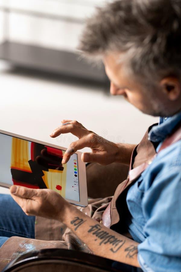 Artiste créatif en tenue de travail assis en studio et utilisant un programme de peinture photographie stock