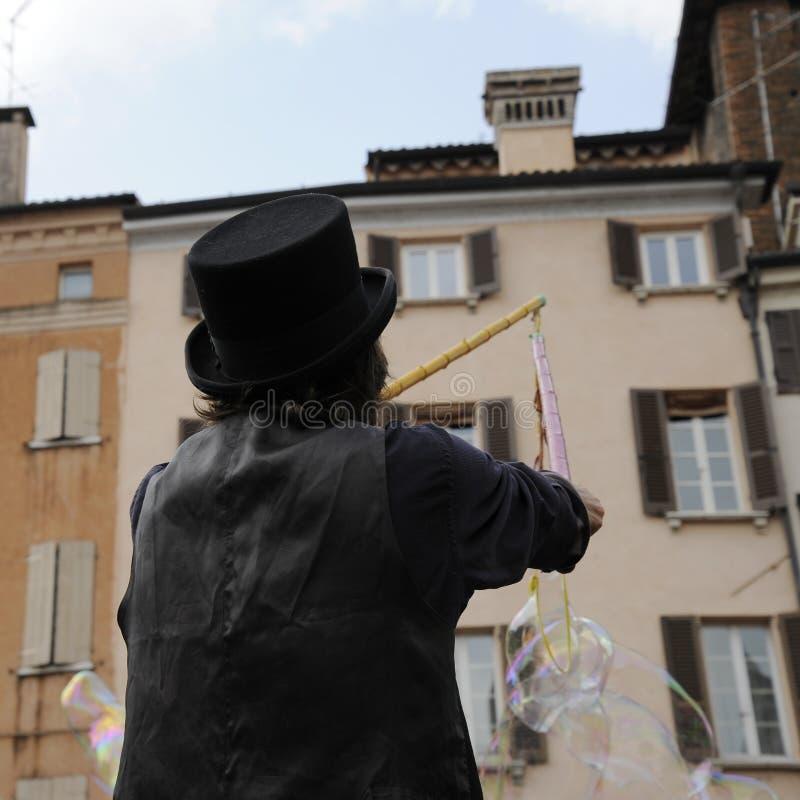 Artiste d'homme avec le chapeau noir qui font des bulles de savon Exposition de bulle de savon sur la rue images stock