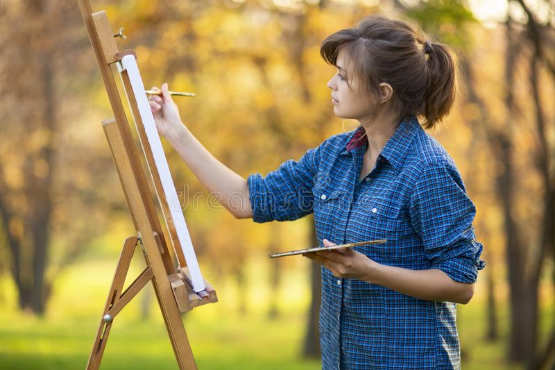 Artiste de femme dessinant une image sur un chevalet dans la nature, une fille avec une brosse et une palette, un concept de la c images libres de droits