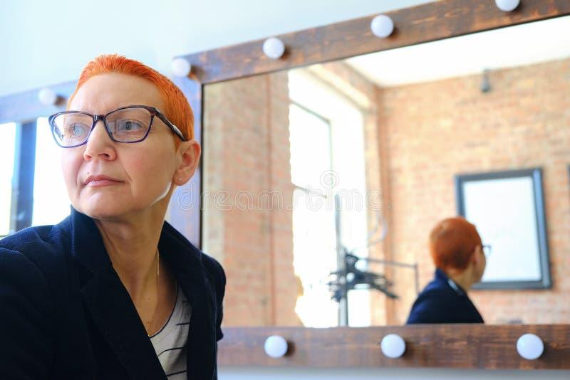 Artiste de fille dans le vestiaire Se reposer devant un miroir avec des lampes Aux yeux de beaux verres ?l?gants photo libre de droits