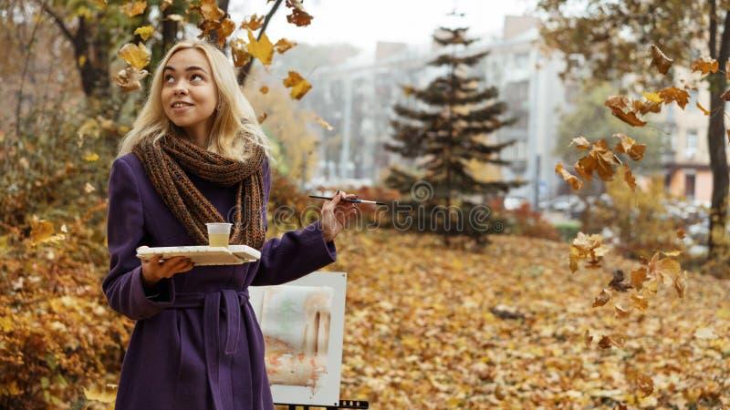 Artiste de jeune fille posant parmi les feuilles en baisse avec le chevalet en parc d'automne photos libres de droits