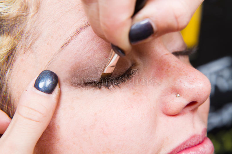 Artiste de maquillage appliquant le maquillage de sourcil photos stock