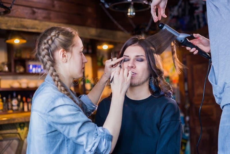 Artiste de maquillage et coiffeur travaillant avec la cliente de femme photographie stock libre de droits