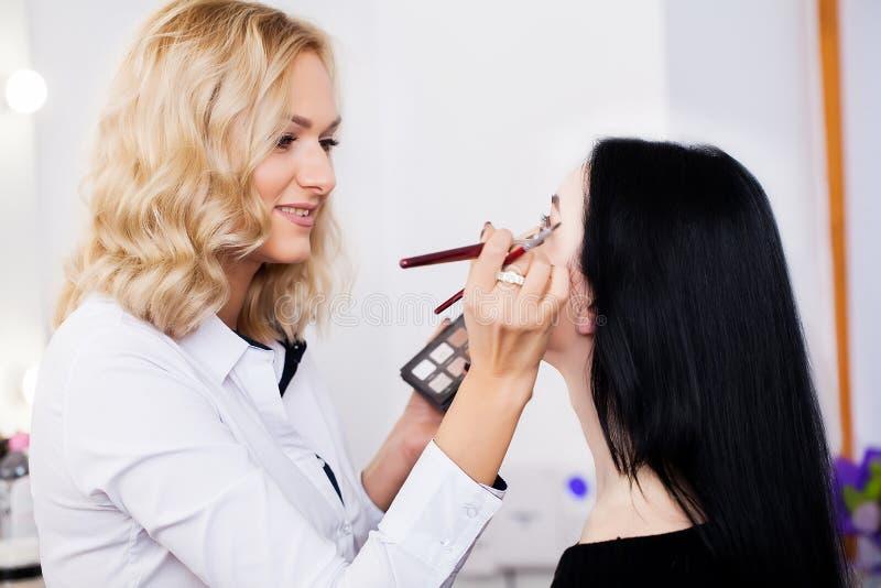 Artiste de maquillage faisant la fille de maquillage dans le salon, concept de beauté photographie stock