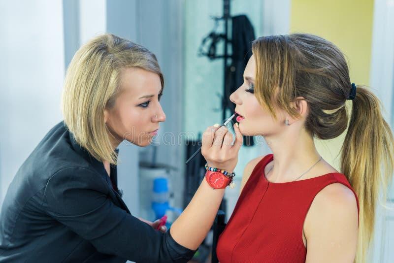 Artiste de maquillage faisant le maquillage fumeux de yeux à la belle jeune fille photos stock