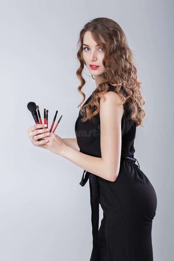 Artiste de maquillage de femme avec le maquillage naturel tenant la brosse de maquillage sur le fond gris photographie stock libre de droits