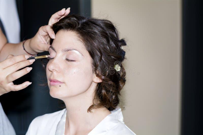 Artiste de maquillage professionnel appliquant le maquillage de mariage photos stock