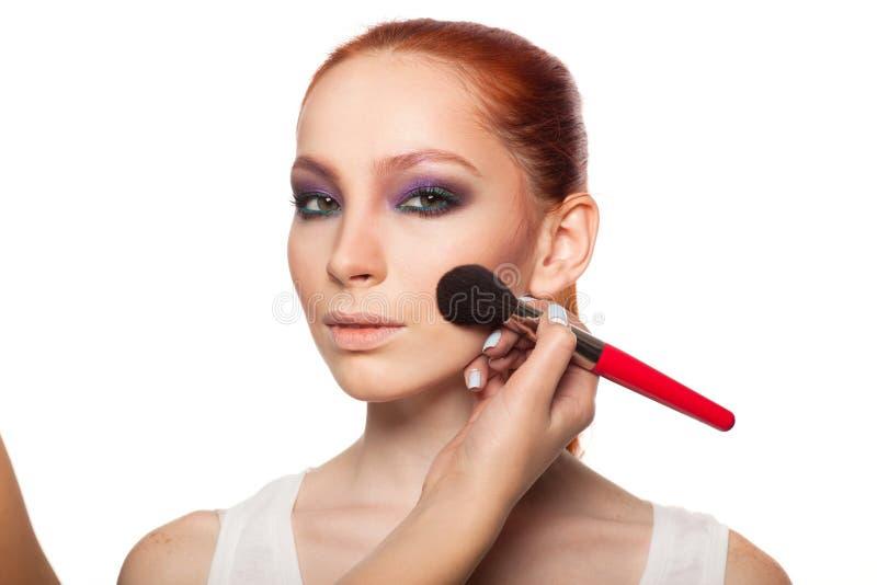 Artiste de maquillage professionnel faisant le charme avec le maquillage rouge de modèle de cheveux Fond d'isolement images stock