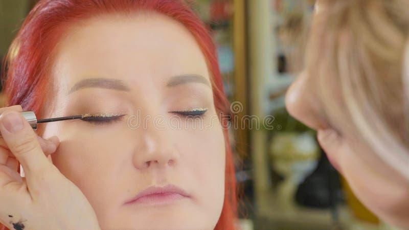 Artiste de maquillage s'appliquant le maquillage à l'oeil modèle du ` s Fermez-vous vers le haut de la vue photo stock