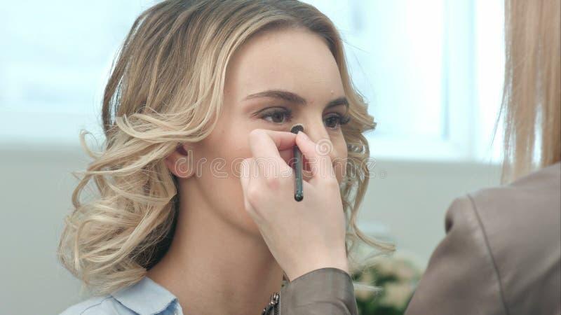 Artiste de maquillage s'appliquant le maquillage de fard à paupières au visage modèle image libre de droits