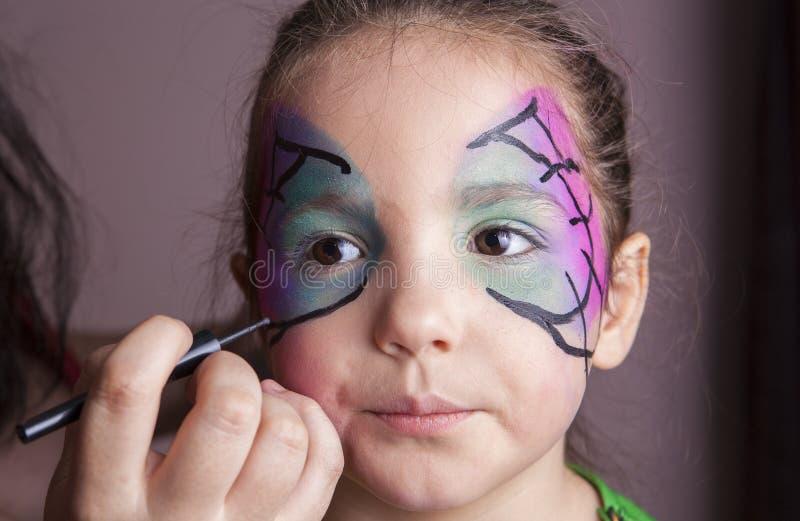 Artiste de maquillage travaillant avec une petite fille devant partie de Halloween photos stock