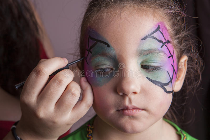 Artiste de maquillage travaillant avec une petite fille devant partie de Halloween images libres de droits