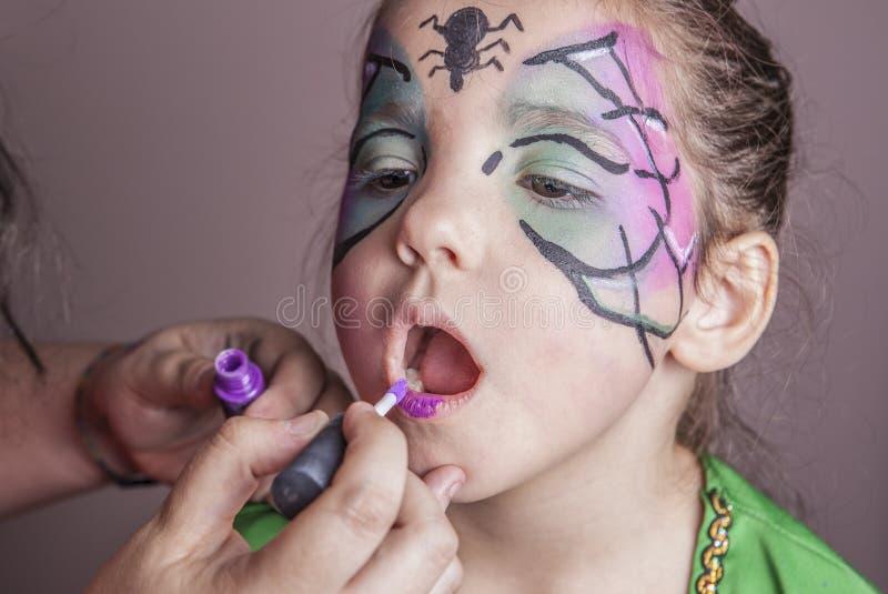 Artiste de maquillage travaillant avec une petite fille devant partie de Halloween image stock