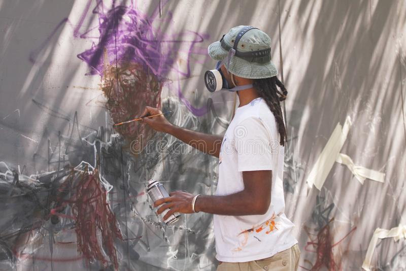 Artiste de rue peignant le graffiti coloré sur le mur - concept d'art moderne avec les murales vivants de peinture urbaine de typ photos libres de droits