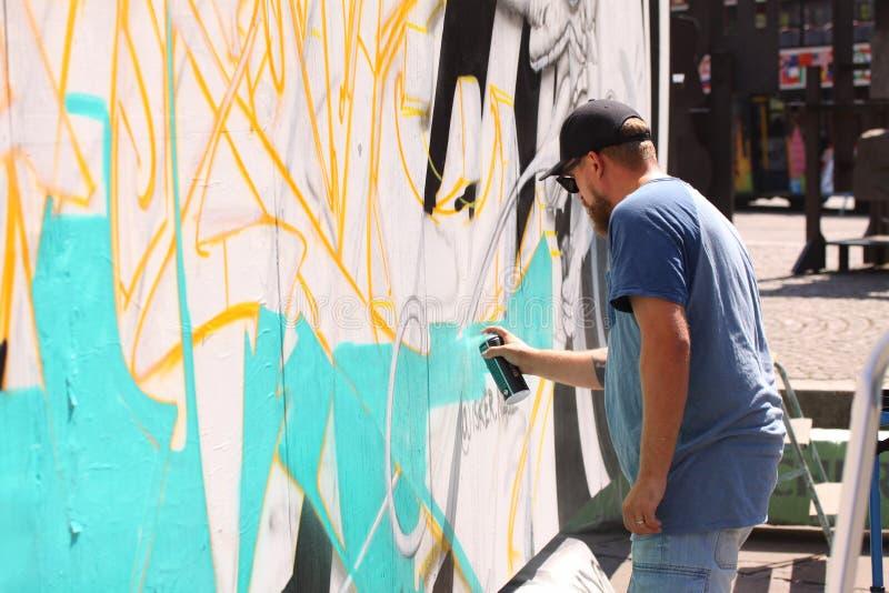 Artiste de rue peignant le graffiti coloré sur le mur - concept d'art moderne avec les murales vivants de peinture urbaine de typ photo libre de droits