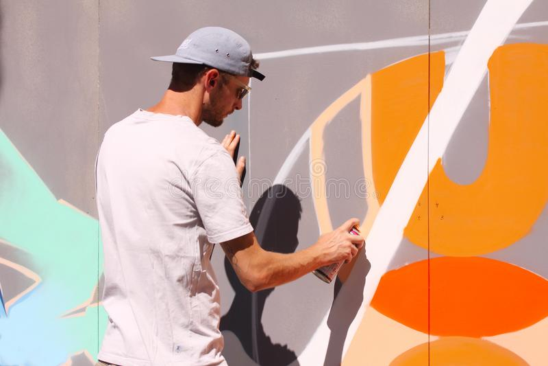Artiste De Rue Peignant Le Graffiti Coloré Sur Le Mur