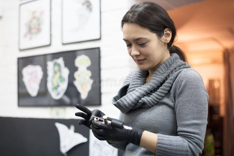Artiste de tatouage de jeune femme se préparant au travail photos libres de droits