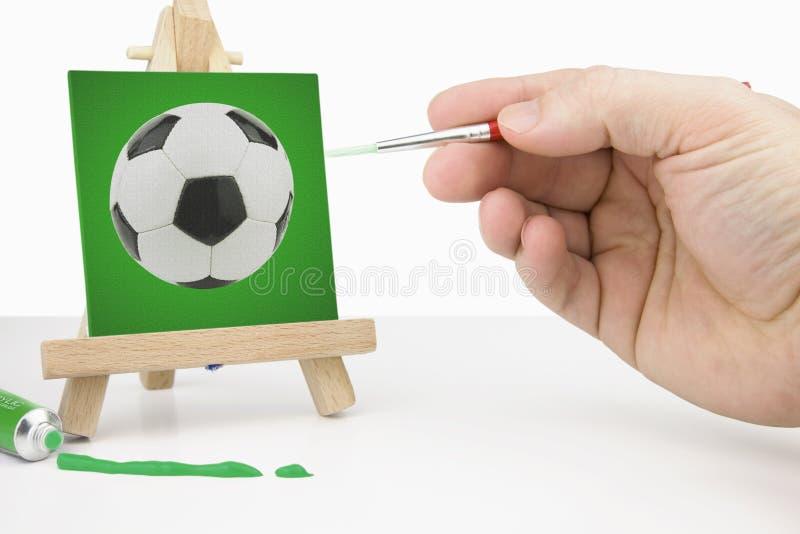 Artiste Easel avec une peinture verte du football de toile et artiste ha photographie stock