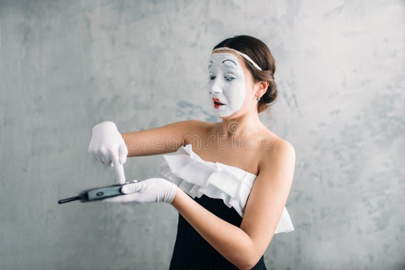 Artiste féminin de pantomime exécutant avec le téléphone portable images stock
