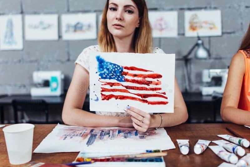 Artiste féminin de sourire lui montrant des travaux, drapeau américain dessiné avec la technique d'aquarelle image libre de droits