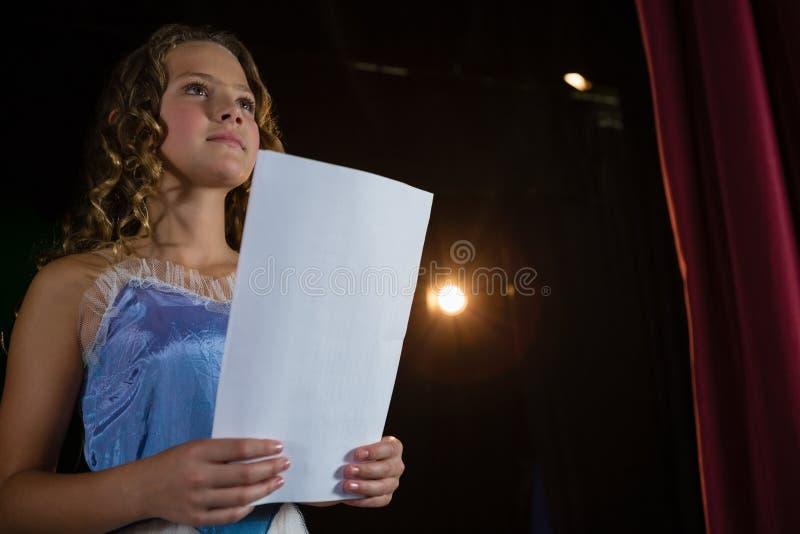 Artiste féminin lisant ses manuscrits sur l'étape images stock