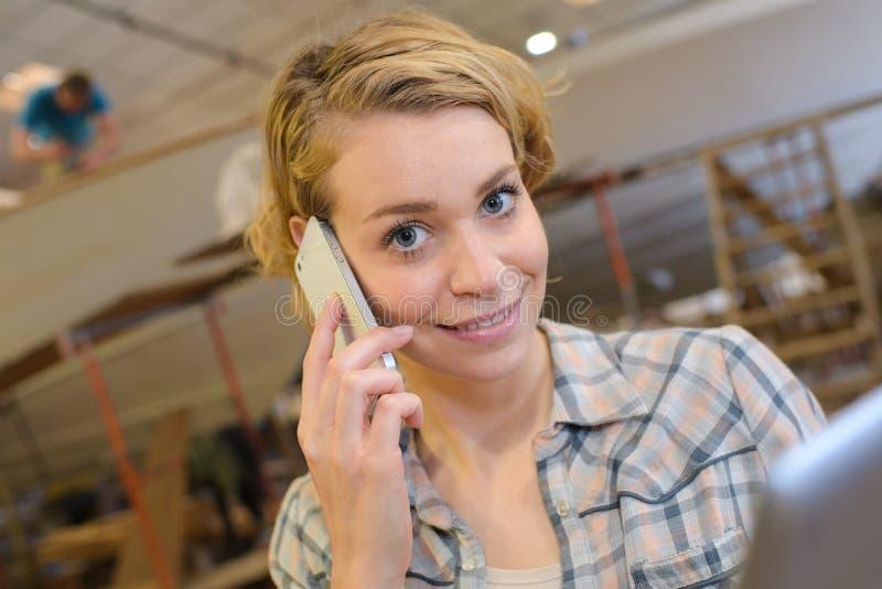 Artiste féminin souriant et parlant au téléphone portable dans l'atelier photo libre de droits